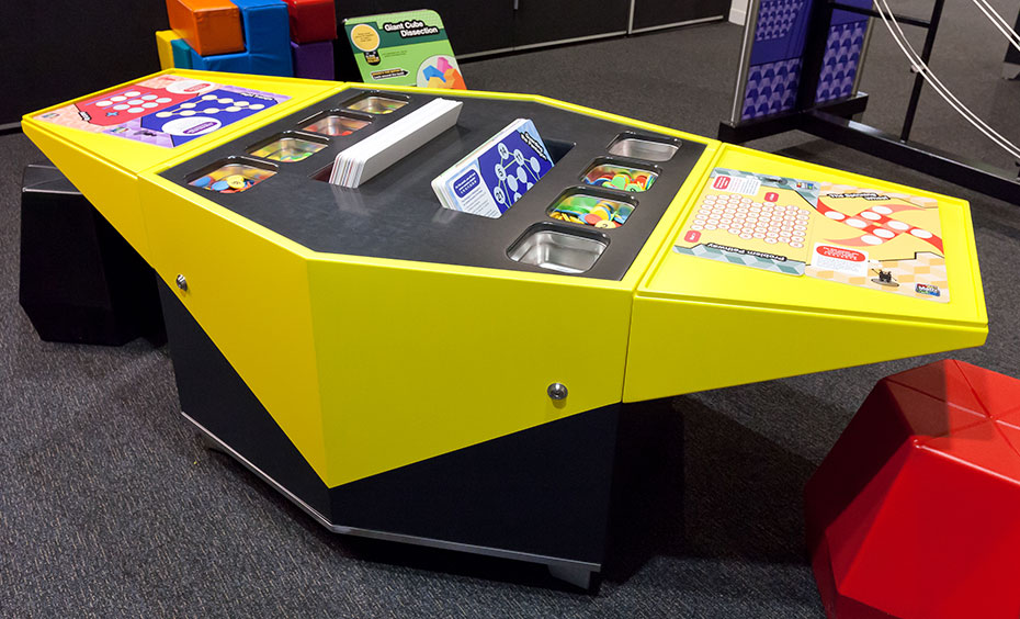 A yellow and black table with puzzle cards and discs in the centre.