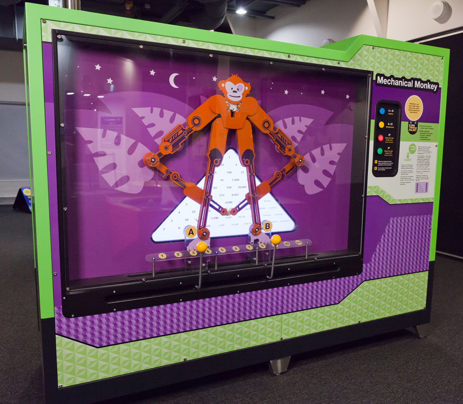 A large rectangular green and purple exhibit with an orange monkey on the left behind glass and coloured buttons on the right information panel.
