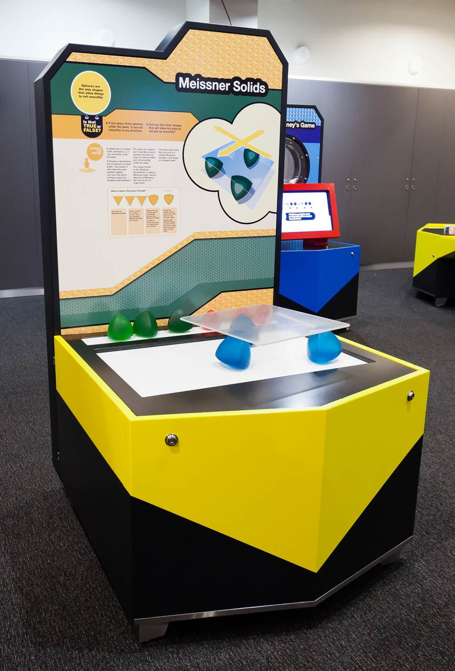 A yellow and black exhibit table and information panel. On the table top sits blue and green solid shapes and a square glass plate.