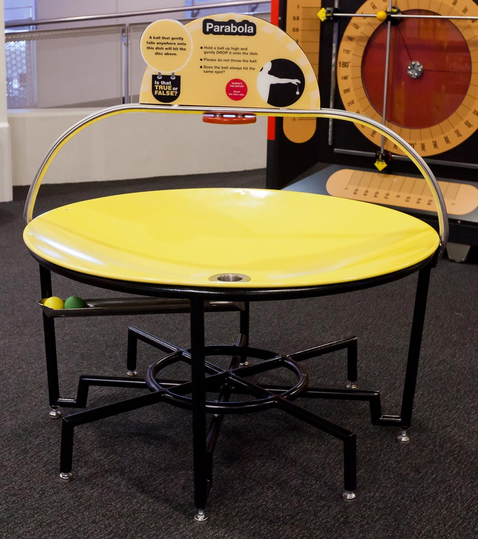 A large yellow parabola disc sits flat on a black.