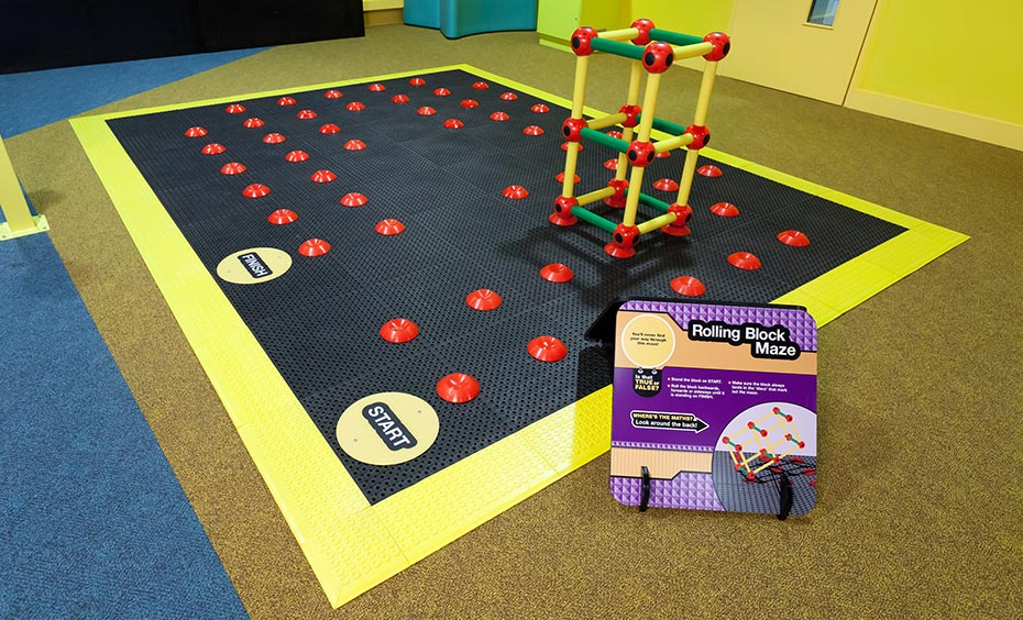 A large black rubber mat with a yellow border and red points throughout the black area has a yellow and red plastic rectangle frame sitting on four of the red points.