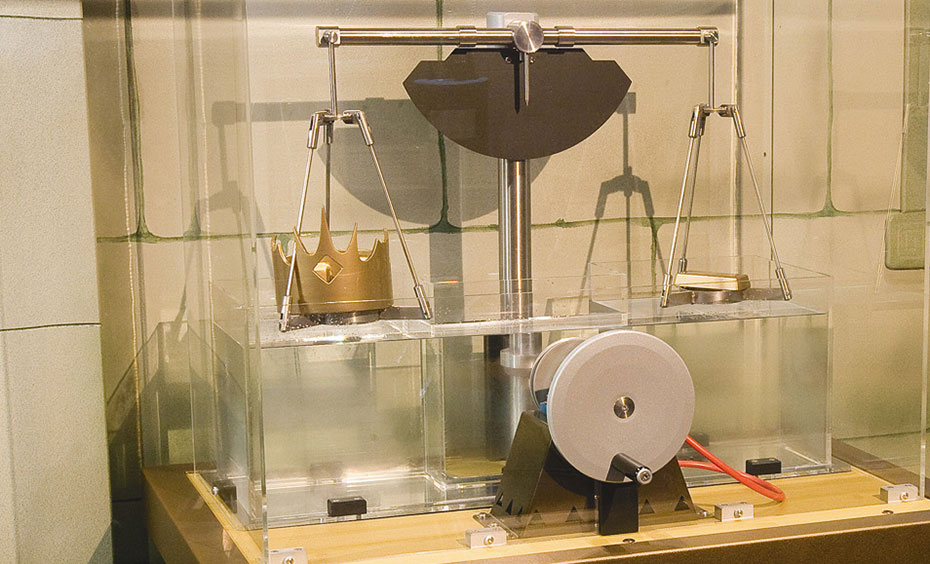 A pretend stone wall in the background with a scale and wheel sitting on a brown table in the forground surround by a clear perspex box.