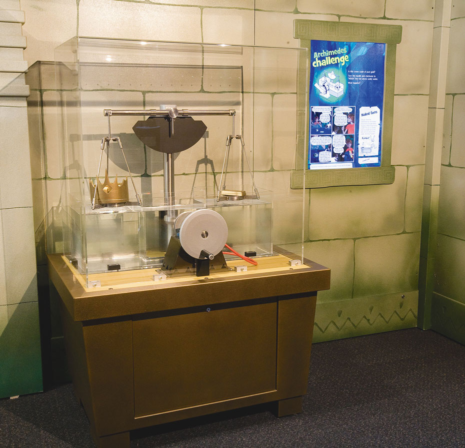 A pretend stone wall in the background with a scale and wheel sitting on a brown table in the forground surround by a clear perspex box. To the right on the wall is a blue information panel titled 'Archimedes Challenge'.