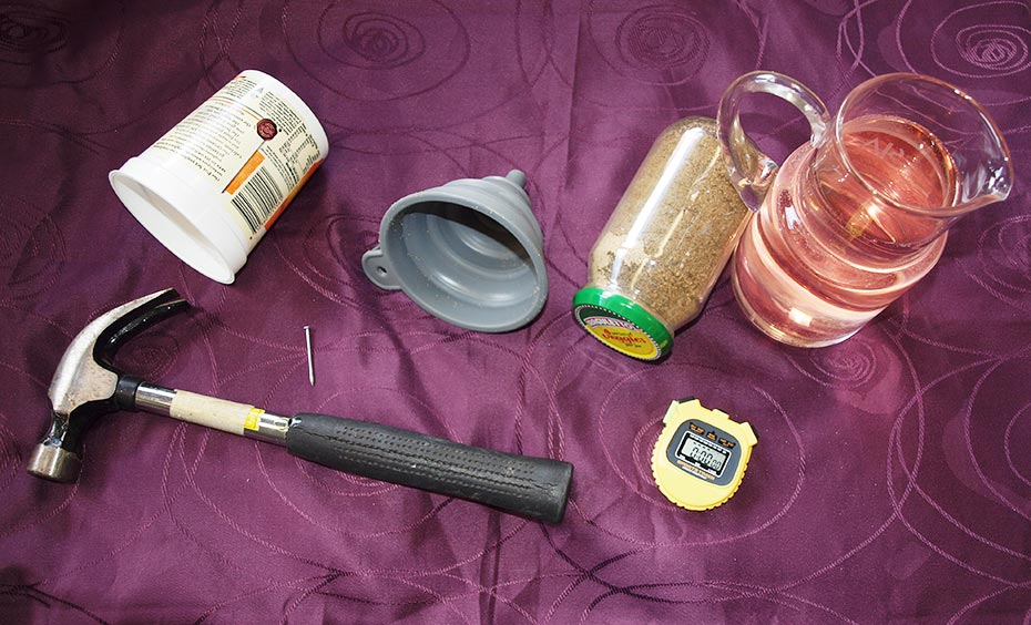 A maroon coloured table cloth with a hammer, plastic cup, nail, grey plastic funnel, glass jar of sand with a green and yellow lid, yellow stop watch and glass pitcher of apricot coloured water siting on it.