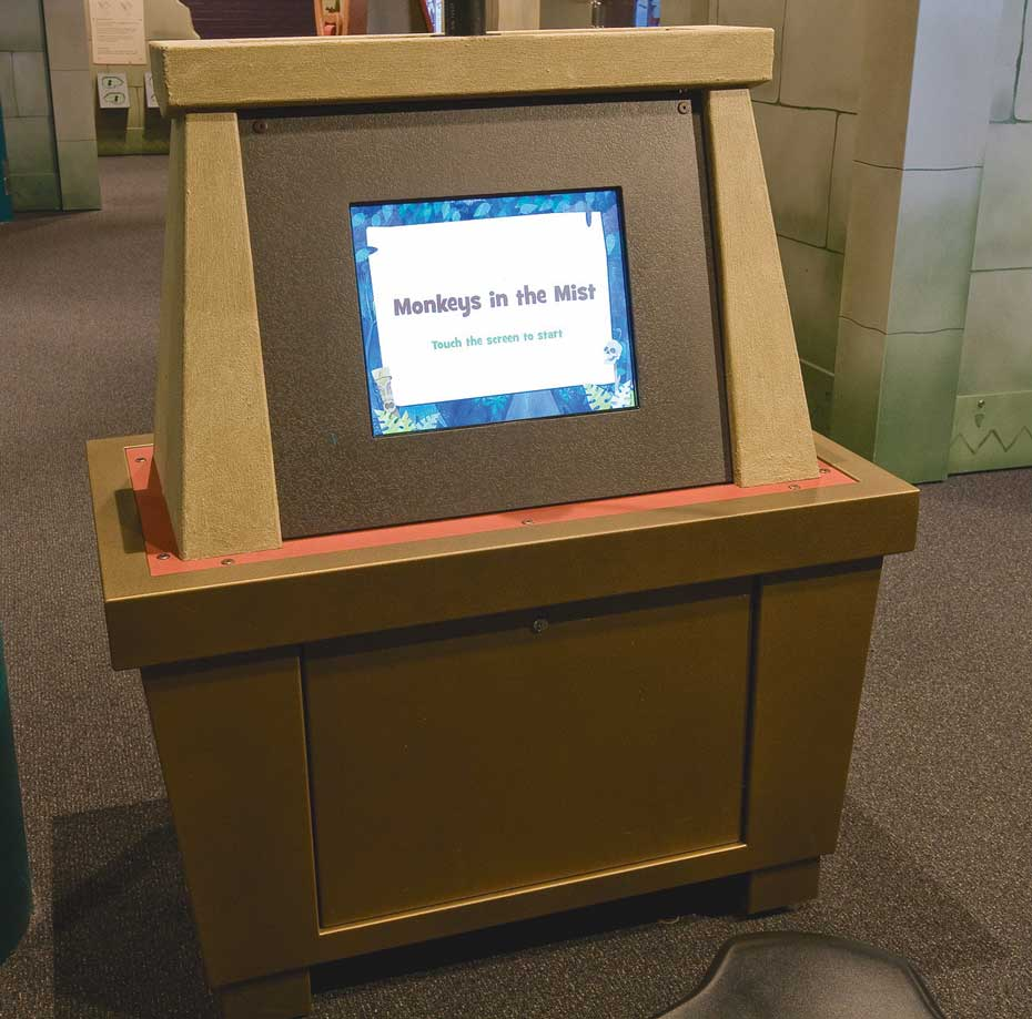 A brown exhibit table with a vertical dispaly area that has a monitor screen and the words 'Monkeys in the Mist' on the screen.