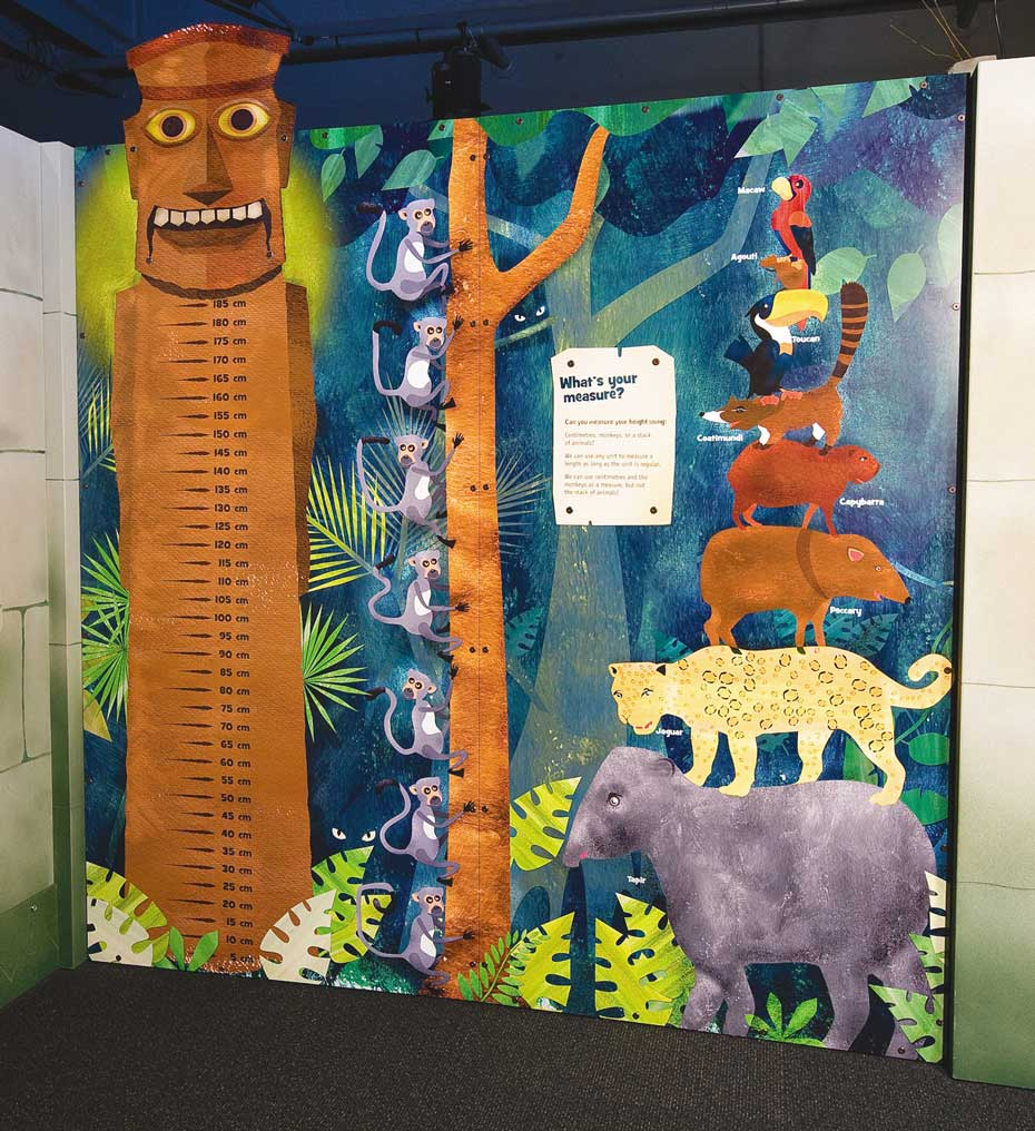 A colourful wall mural with a large totem pole on the left that has measurement markings in centremetres from top to bottom. The mural also has monkeys in a tree and various animals stacked upon one another from large to small.