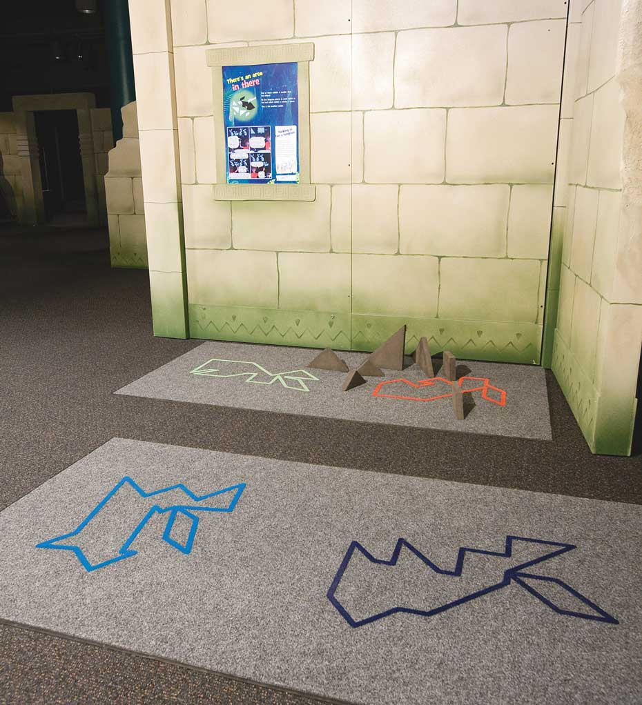 A carpeted area in which there are four abstract rabbit shapes on the carpet. In the background is a fake stone wall with a blue, white and green information panel.