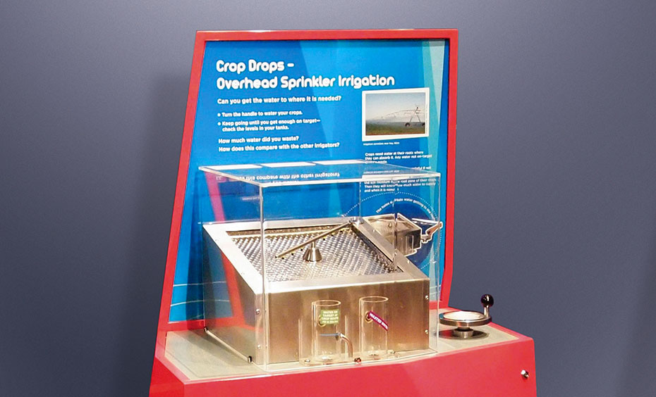 "A red exhibit with a blue information panel at the back, and the title ""Crop Drops - Overhead Sprinkler Irrigation'. In a clear perspex box in front of the panel is a stainless steel box with a spinning irrigation arm on it."