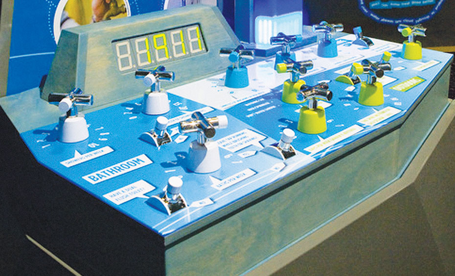 A blue and white exhibit with lots of taps and switch in front of digital numbers and a vertical information panel titled 'Water Footprint'