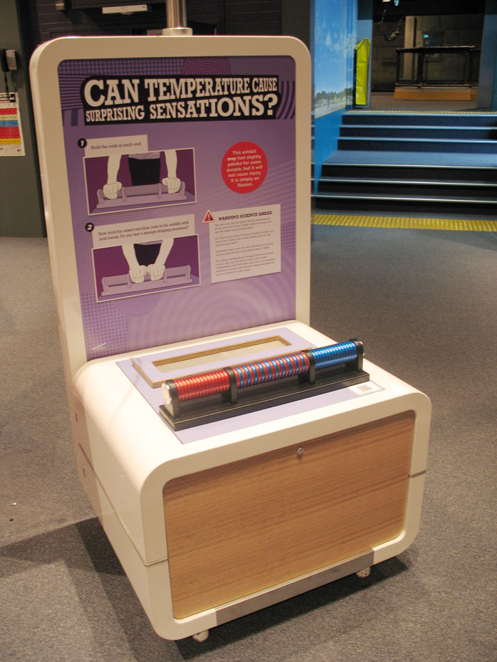 An exhibit table and headboard with the text 'Can Temperature Cause Surprising Sensations?'. There are a row of discs on the table top.