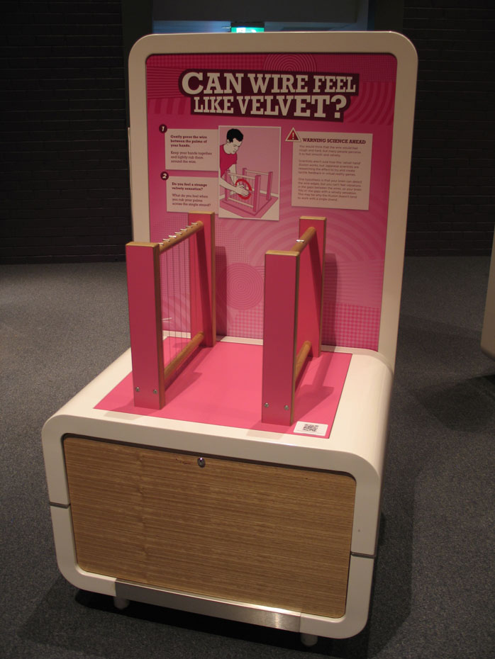 An exhibit table and display board, with vertically strung wires on timber frames. The title 'can wire feel like velvet?' appears on the backboard.