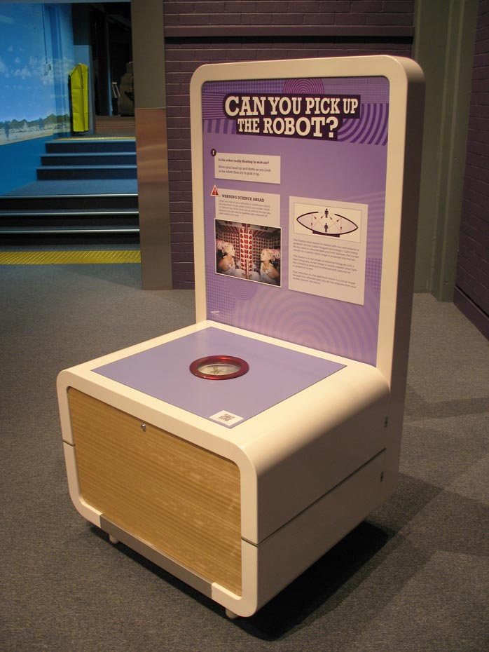 A cream and purple coloured exhibit table with headboard that has 'Can you pick up the robot?' written upon it.