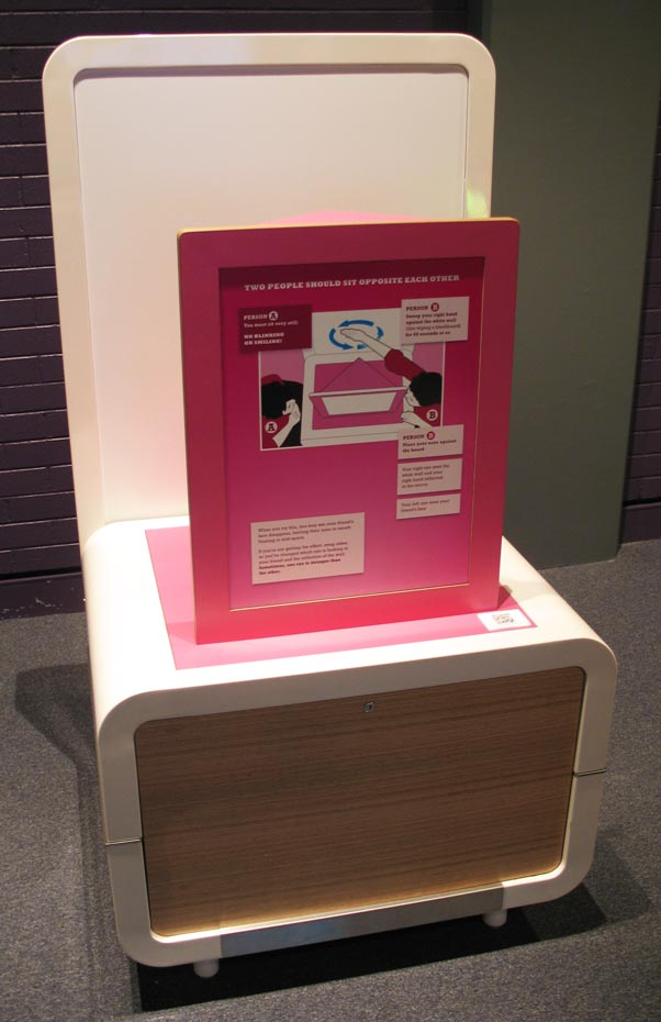 A cream and pink exhibit table with a pink information panel in the centre.