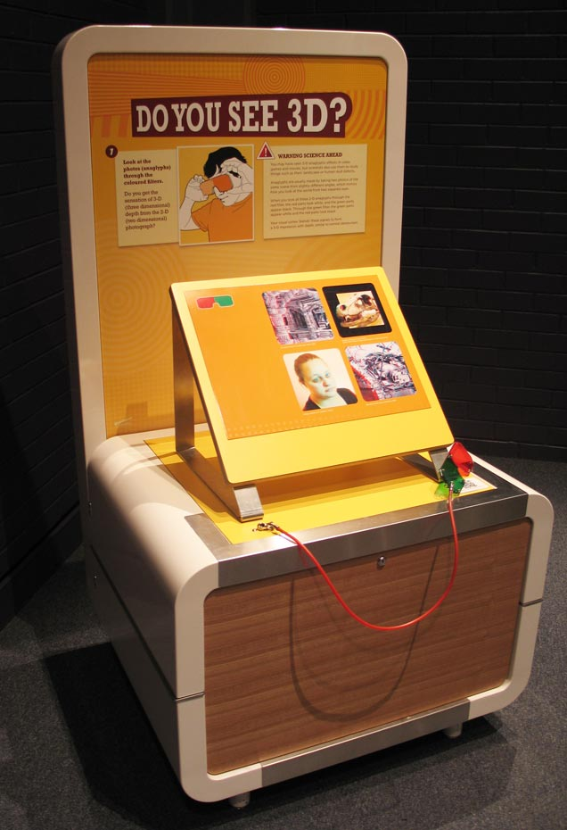 A cream, orange and yellow exhibit table and backboard, with the title 'Do you see 3D?