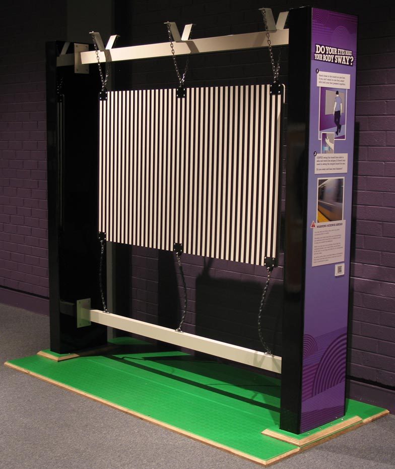 A large pruple and cream coloured vertical exhibit, that has a series of vertical timber pieces hung between two large panels.