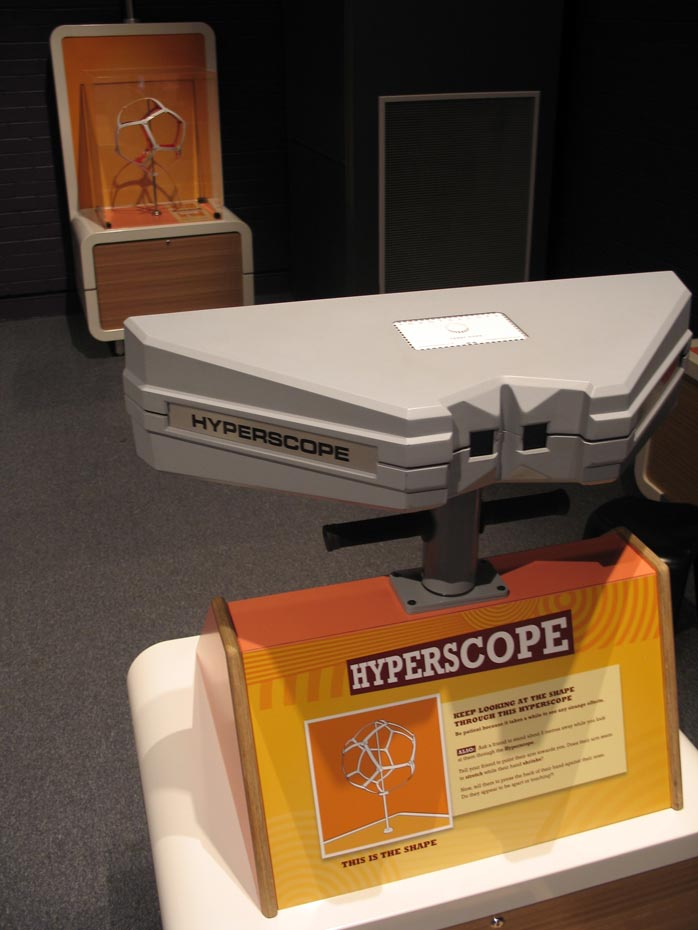 Two orange and cream exhibits about 5 metres apart. The text 'Hyperscope' is on the nearest exhibit.