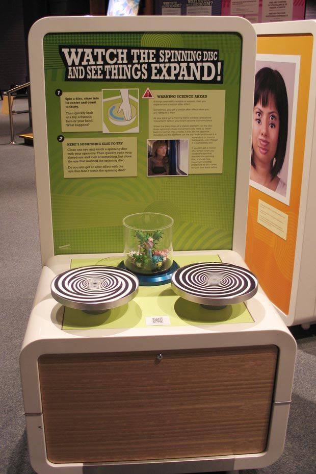 A cream and green exhibit table and backboard with the title 'Watch the spinning disc and see things expand!. Two horizontal discs sit on the table top with black and white spiral patterns.