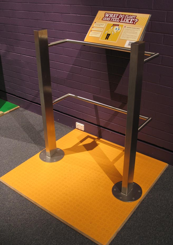 A yellow sign with the title 'what do floaty arms feel like?' supported by a stainless steel frame that is bolted to a yellow floor mat.