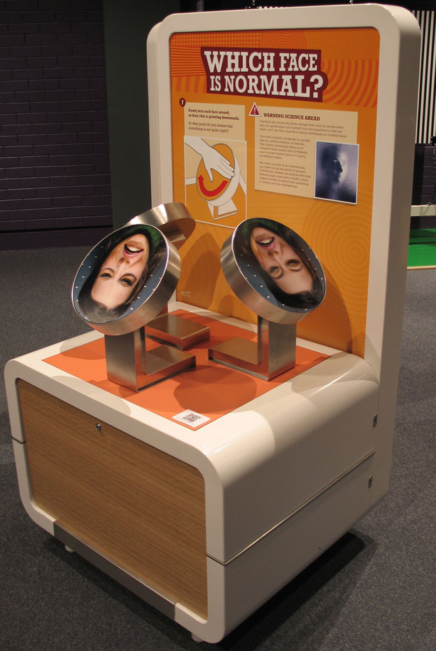 A woman's face printed onto a round steel disc, sits on an exhibition table