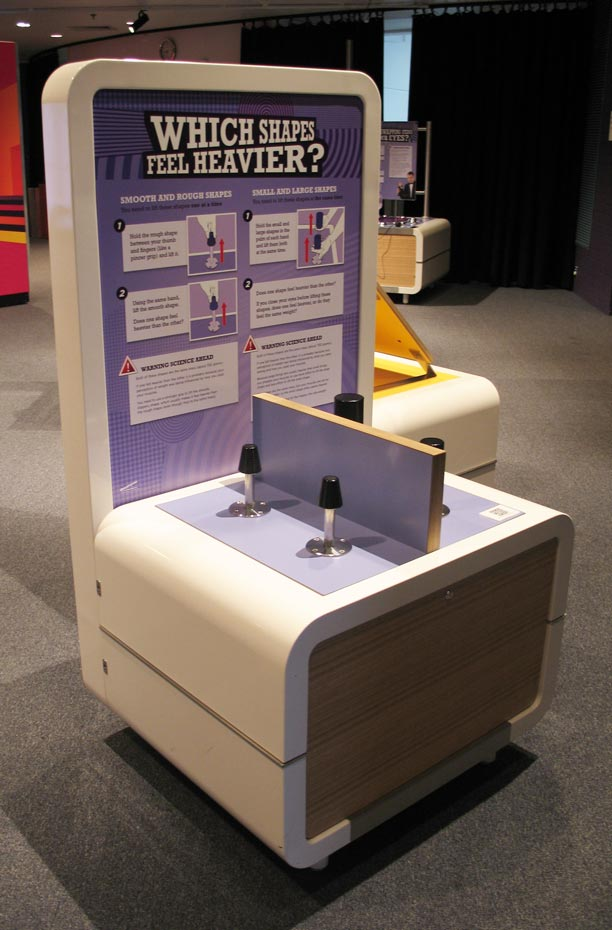 A cream and purple coloured exhibit table and headboard with the text 'Which shapes feel heavier?'. On the table top sits a divider board with four black cylindrical objects.