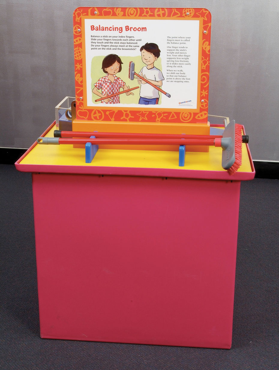 A red exhibit table with a yellow top and a vetical orange and white information panel. In front of the panel is a red and grey broom.