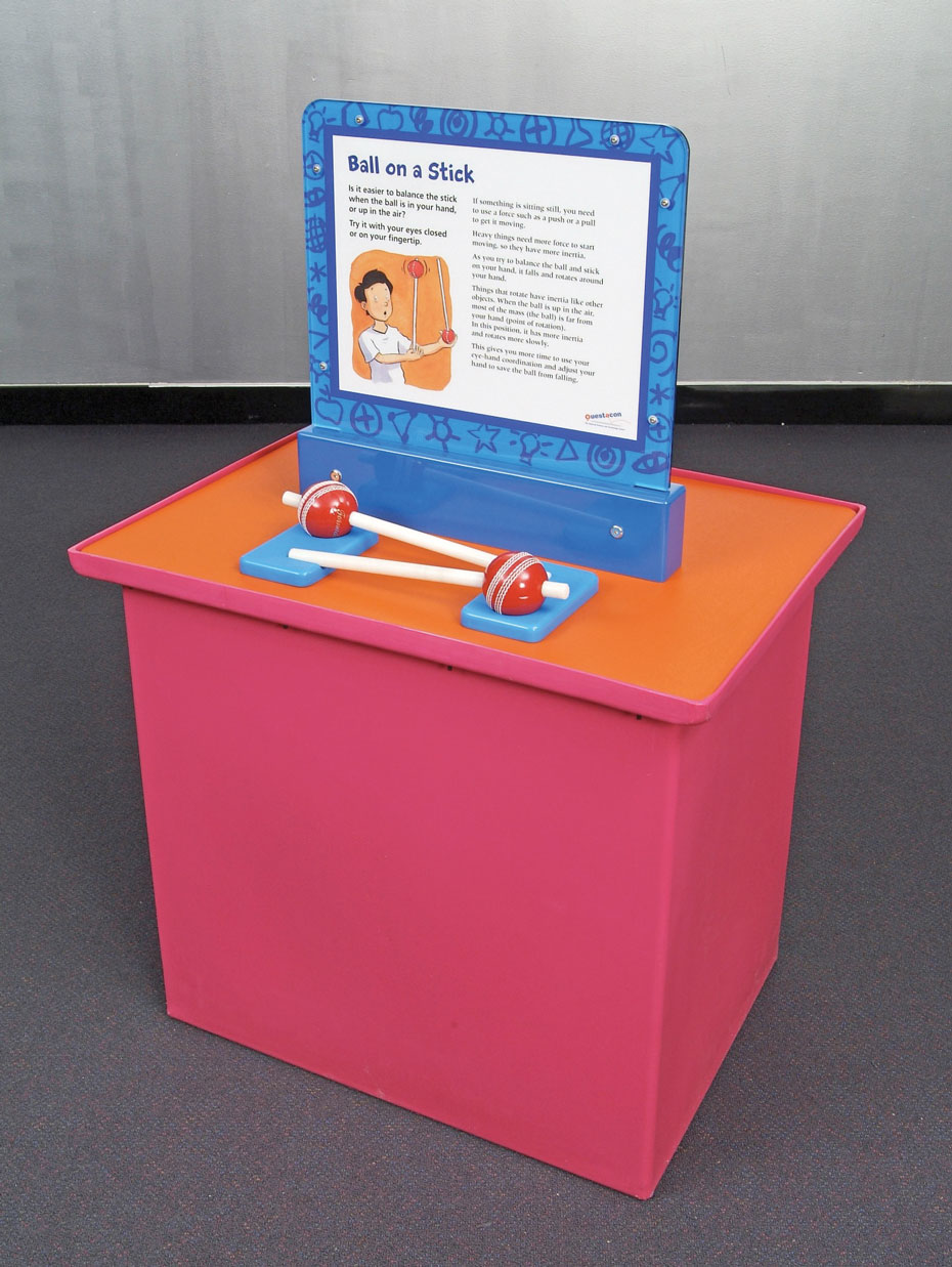 A pink and orange display table with a vertical blue information panel on top. In front of the panel, are two red cricket balls which each have a shite stick going through them.