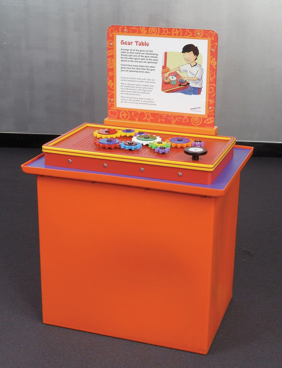 An orange, purple, red and yellow exhibit table with a white and orange information panel at the back. On top of the table are a series of colourful gears.