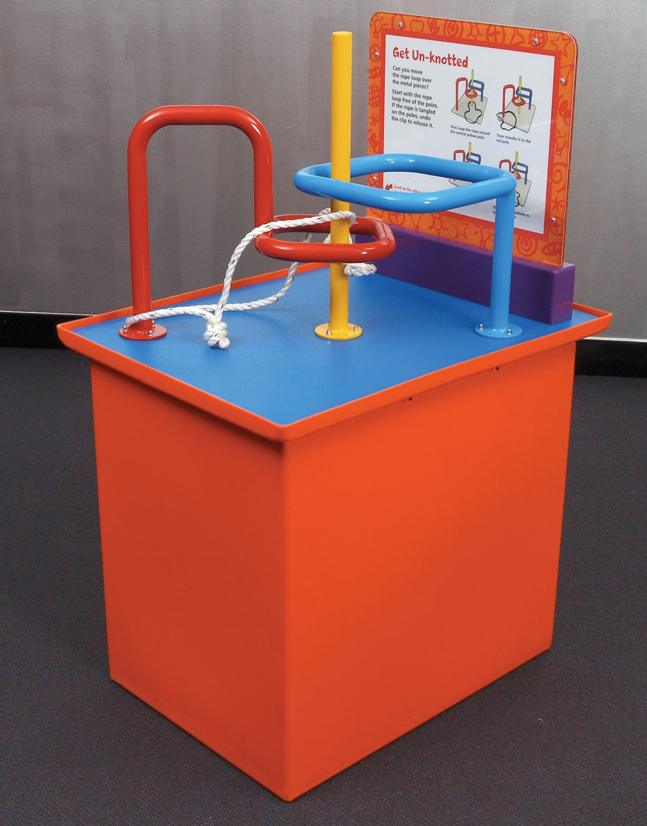 An orange and blue exhibit table, with a white and orange information panel at the back. Red yellow and blue steel bars rise out of the table top, and are bent into different shapes. A piece of white rope with a knot in it is threaded between the bars.