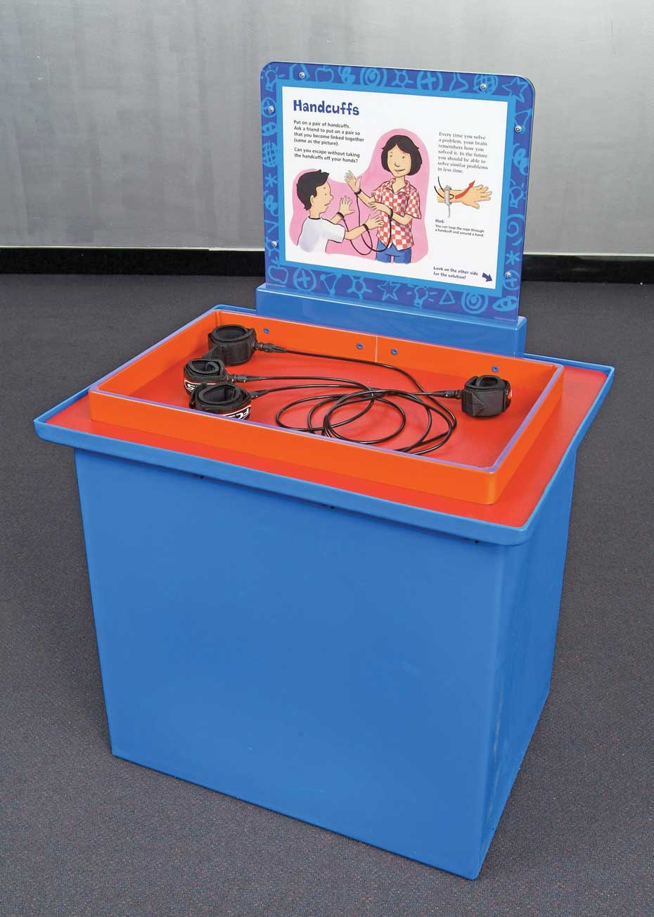 A blue and orange exhibit table with a white and blue information panel behind it. On top of the table is an orange tray with four black velcro handcuffs that have cords between them.