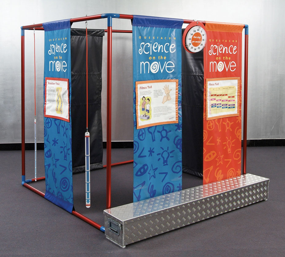 A large red and blue cube frame that has blue and orange banners running from top to bottom with different information on each. In front on the grey carpet is a long checkerplate steel box.