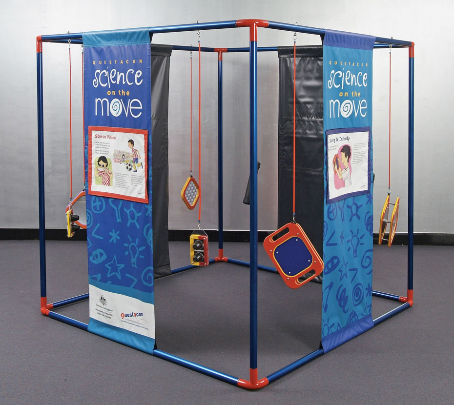 A large red and blue cube frame that has blue and orange banners running from top to bottom with different information on each. There are orange and yellow objects hanging from the frame.
