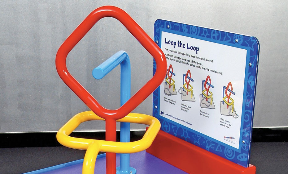 A blue exhibit table with a blue, white and red information panel on top. On the top of the table intertwined red, blue and yellow steel bars, with a white rope with a knot tied in it, that is around the yellow bar.