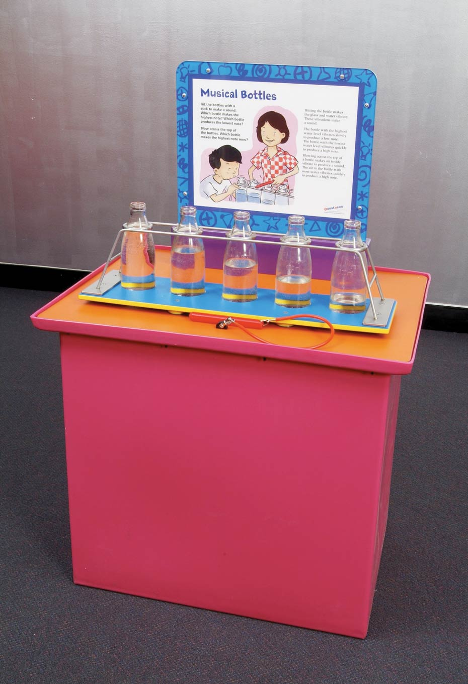 A red and orange exhibit table, with a white and blue information panel at the back. On top of the table are 5 milk bottles filled with different levels of water.