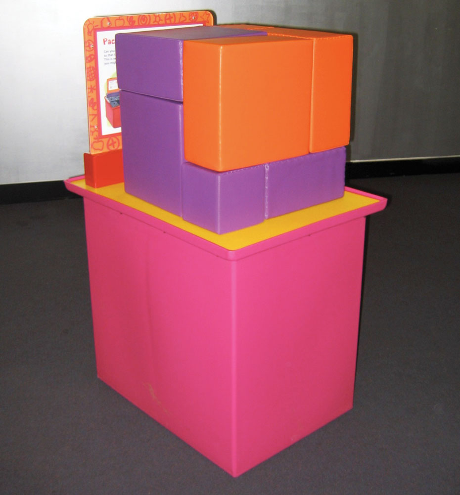 A pink and yellow exhibit table, with a white and orange information panel at the back. On the table sits purple and orange soft square shapes that all fit together to form a cube.