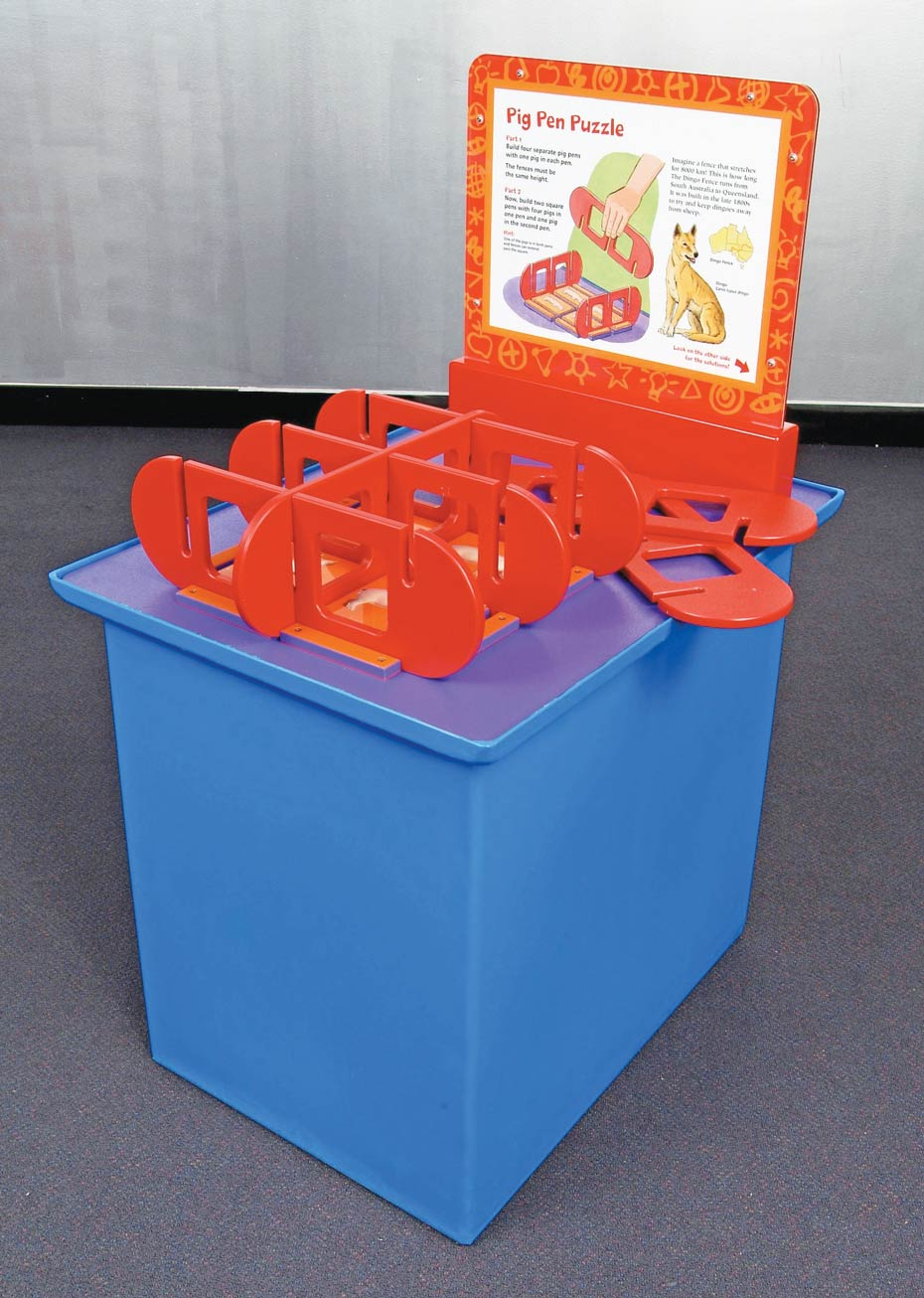 A purple exhibit table, with a white and orange information panel at the back. On top sits a series of red puzzles pieces that fit together to form enclosures.