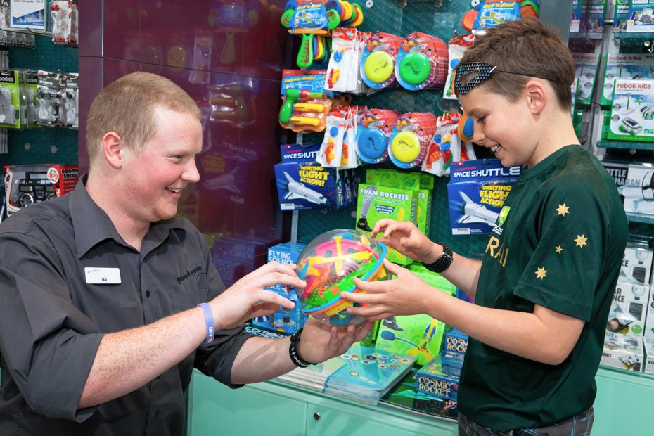 A man and boy are holding a round toy and are both in front of a display stand of toys and science materials in a shop.