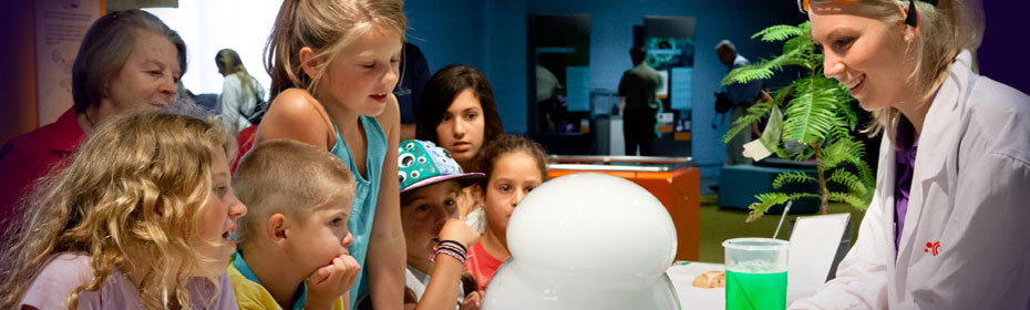 A young woman dressed in a lab coat is demonstrating how bubbles are made to a bunch of young school kids.