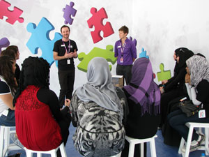 A group of women in middle eastern dress are sitting in a semi-circle listening to a man and woman talking.