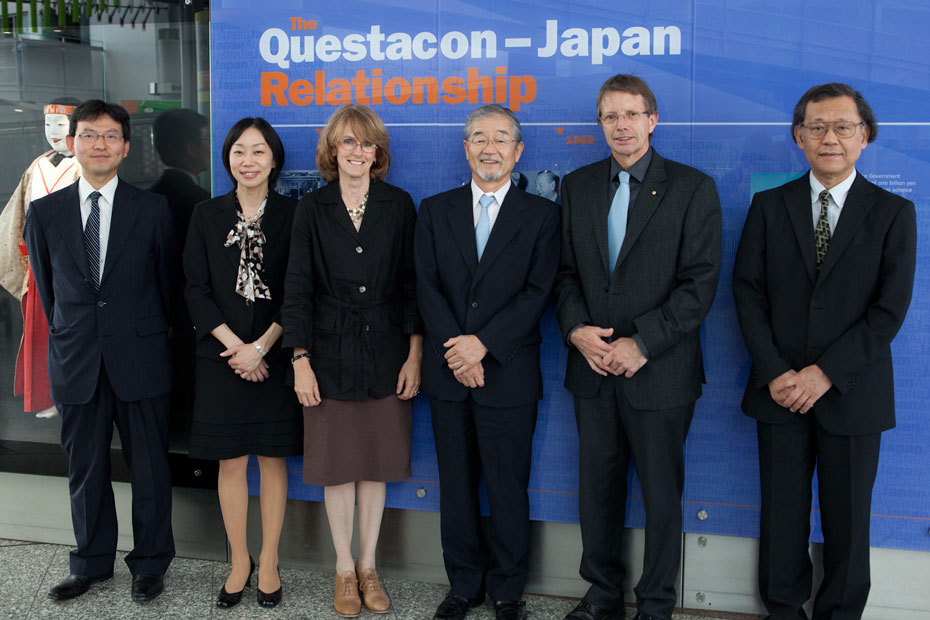 4 men and 2 women all dressed in dark business dress are standing in front of a purple background with the words 'The Questacon-Japan Relationship'