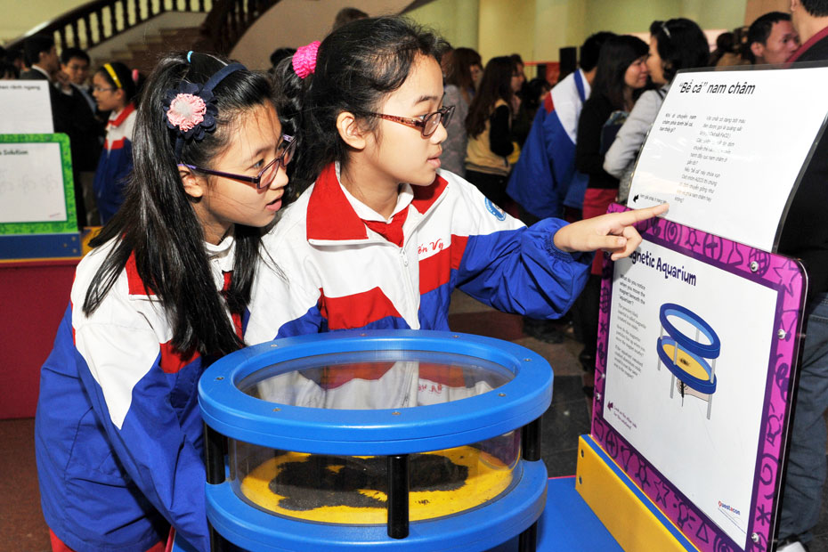 Two school girls looking at a purple and white information panel with English and Vietnamese writing displayed, and a blue and yellow ringed object sits on the exhibit table in front of them.