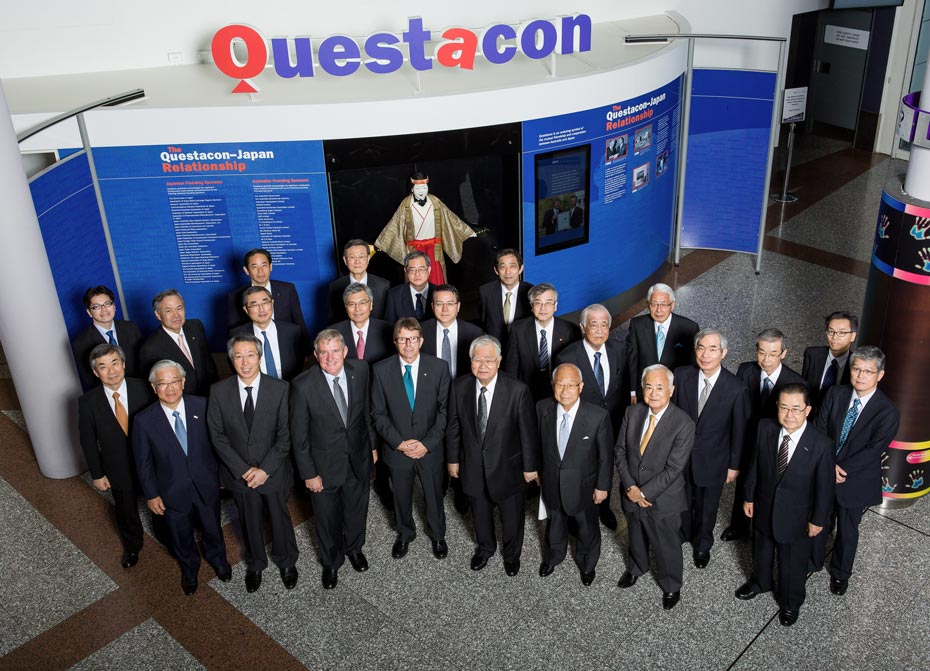 A group of men all in suits standing in front of a wall with information on it and the sign Questacon at the top.