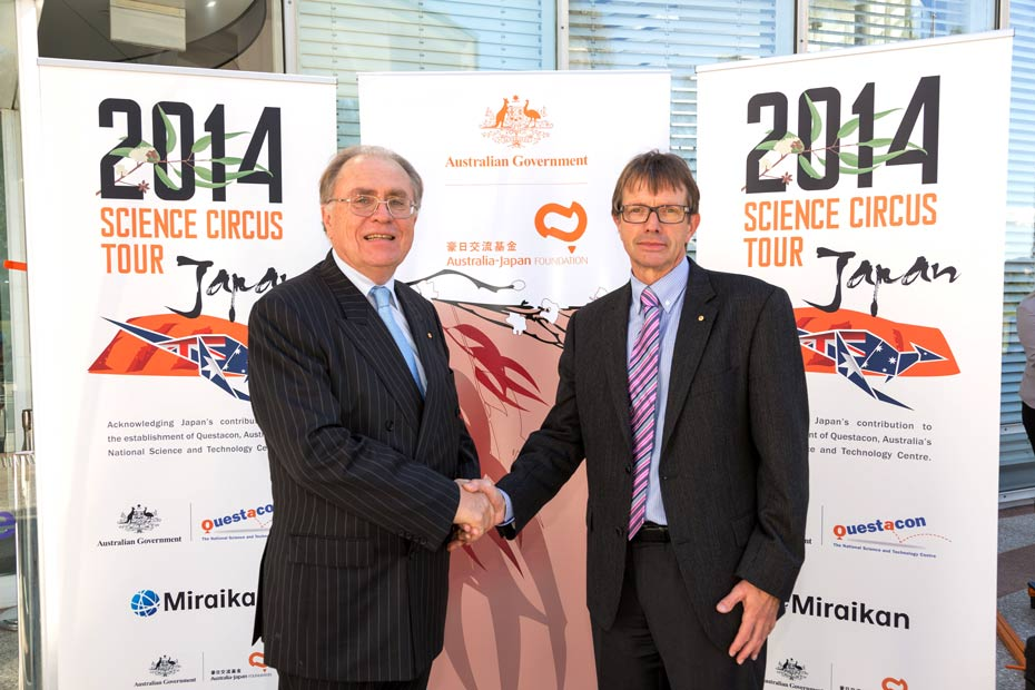 Two men in suits shaking hands and standing in front of three vertical banner signs that are headed 2014 Science Circus Tour and Australian Government.