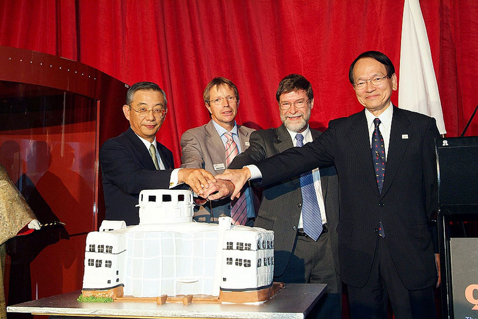 Mr Ueda, Professor Durant, Mr Grahame Cook and Mr Masaaki Ono stand in a row behind a large cake in the shape of the Questacon building. Together, the four men hold a large knife and cut the cake, while smiling.