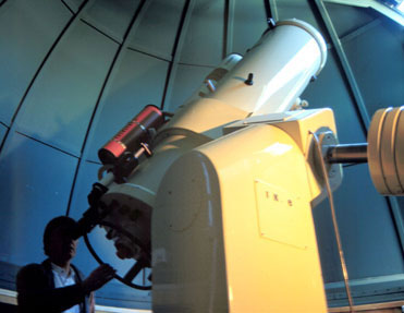 The central image is a large cylindrical white telescope. The base of the telescope is in the lower left, the open end of the telescope is pointing to the upper right. An observer looks into the eyepiece at the base of the telescope. In the background is the inside of the domed roof of the observatory in which the telescope sits.