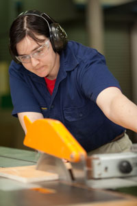A woman with a work shirt, safety goggles and hearing protection is cutting a piece of timber on a saw table.