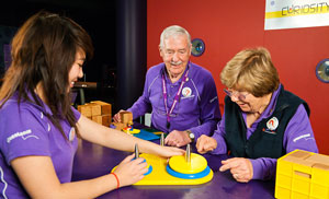 A young woman, a elderly man and a elderly woman wearing purple Questacon shirts are standing in front of a red wall around a purple table. On the table us a yellow puzzles with blue and yellow discs.