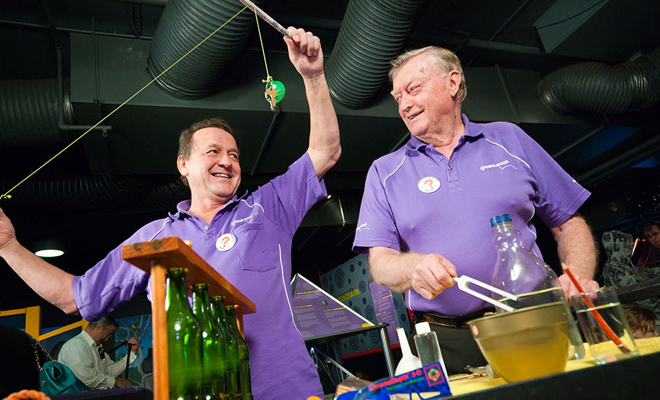 Two men in purple shirts standing in front of various science experiments.