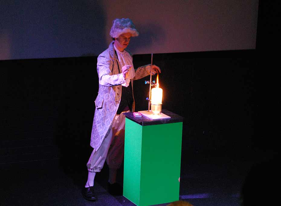 A man in 17th Century costume performs an experiment with fire.