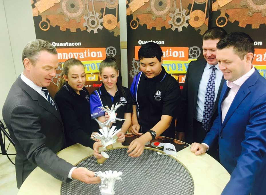 Minister Pyne building flying cups over a wind table with three students and two men in suits