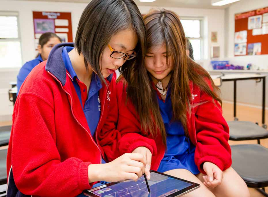 Two girls use a Samsung tablet